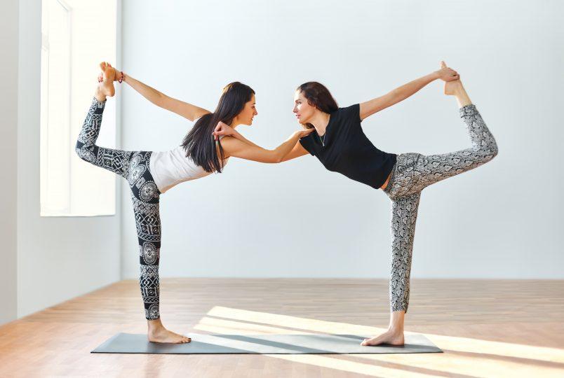 Två kvinnor i en yogaposition