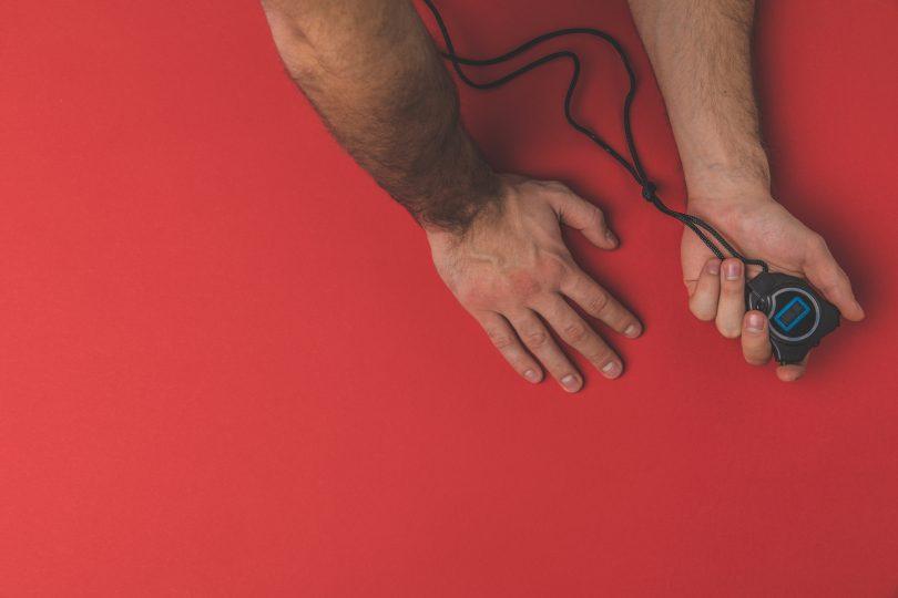 Tidtagarur i manlig hand mot röd bakgrund