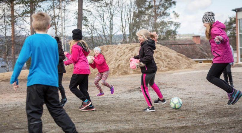 Barn som leker med en boll på skolgården