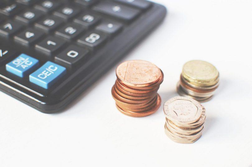 Mynt på hög tillsammans med miniräknare