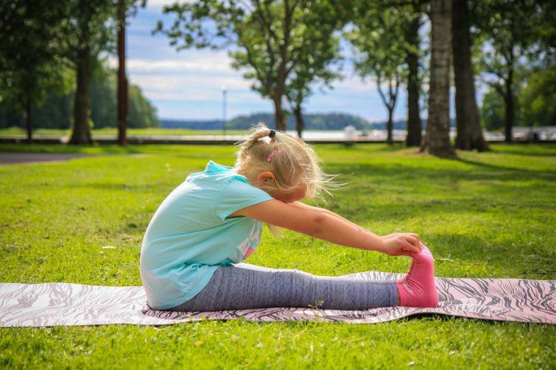 Sittande framåtböj görs av en flicka på en grön gräsmatta