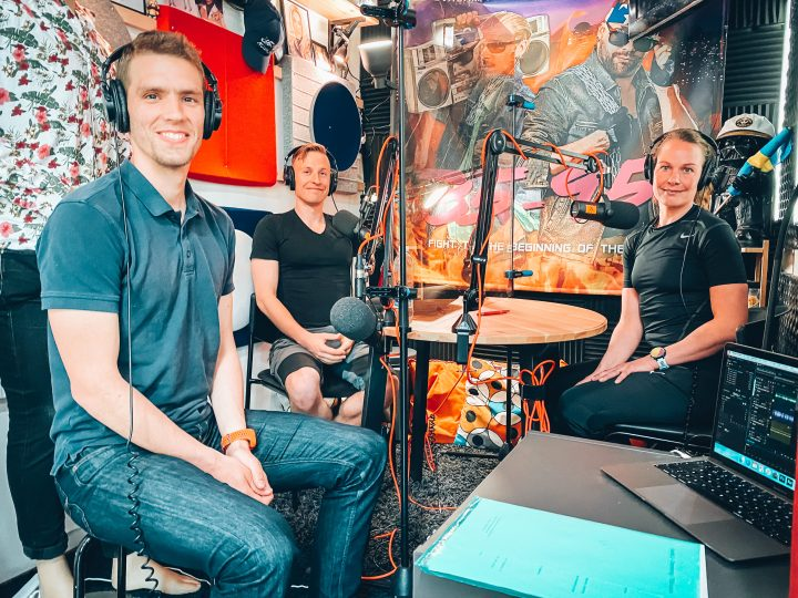 Fredric Portin på besök i poddstudion. Tillsammans med Henrika och Wille sitter de kring ett studiobord med hörlurar och mikrofoner.