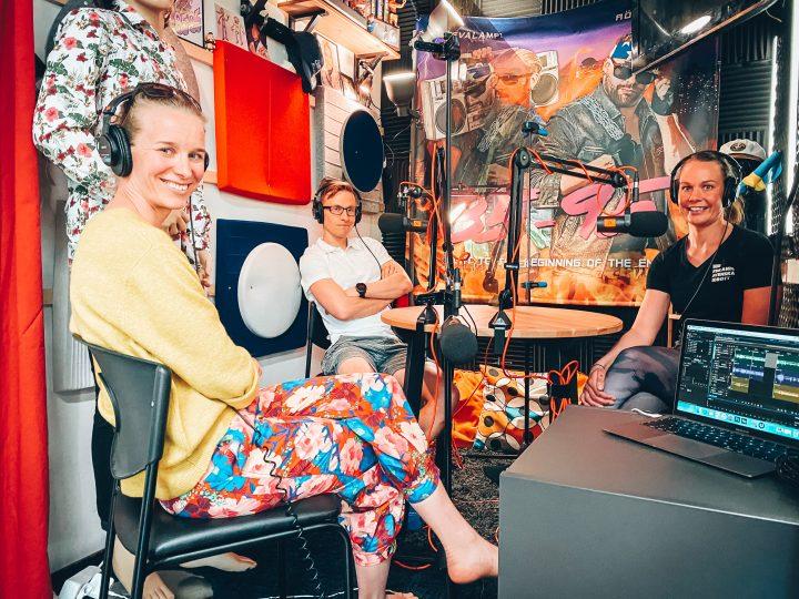 Jasmina Glad-Schreven på besök i poddstudion. Tillsammans med Henrika och Wille sitter de kring ett studiobord med hörlurar och mikrofoner.