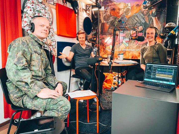 Harri Paukku på besök i poddstudion. Tillsammans med Henrika och Wille sitter de kring ett studiobord med hörlurar och mikrofoner.
