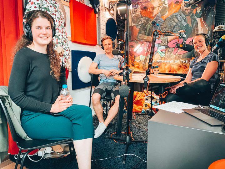 Sonja Fredriksson på besök i poddstudion. Tillsammans med Henrika och Wille sitter de kring ett studiobord med hörlurar och mikrofoner.