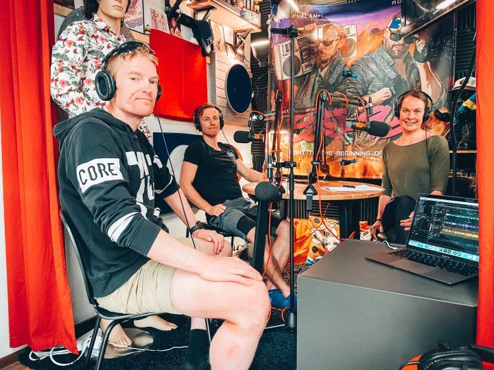 Markus Lindqvist på besök i poddstudion. Tillsammans med Henrika och Wille sitter de kring ett studiobord med hörlurar och mikrofoner.