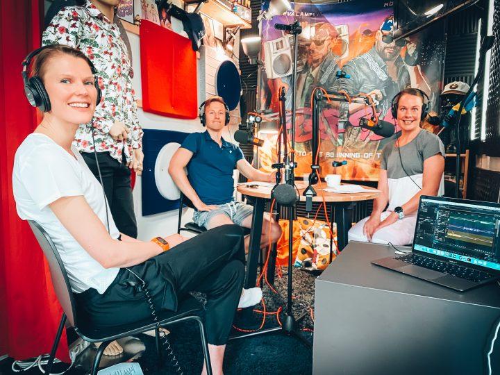 Saara Norrgrann på besök i poddstudion. Tillsammans med Henrika och Wille sitter de kring ett studiobord med hörlurar och mikrofoner.