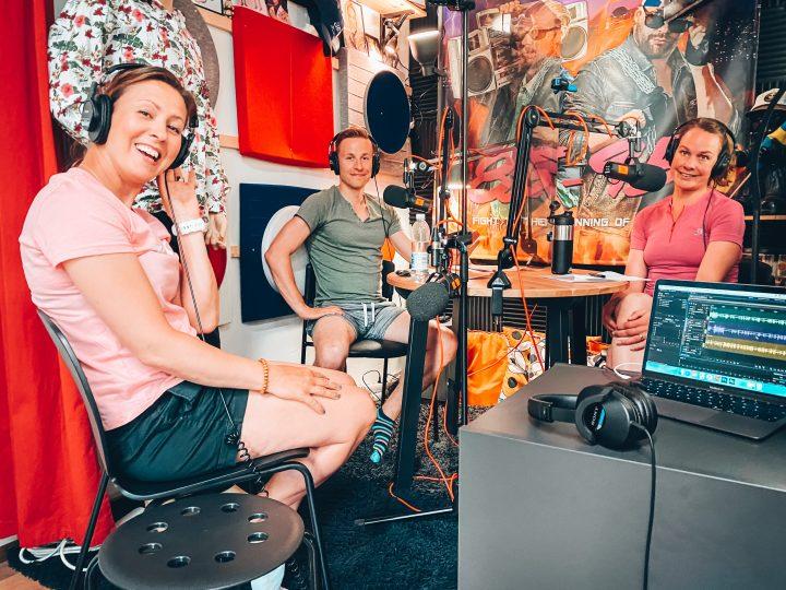 Petra Stenman på besök i poddstudion. Tillsammans med Henrika och Wille sitter de kring ett studiobord med hörlurar och mikrofoner.