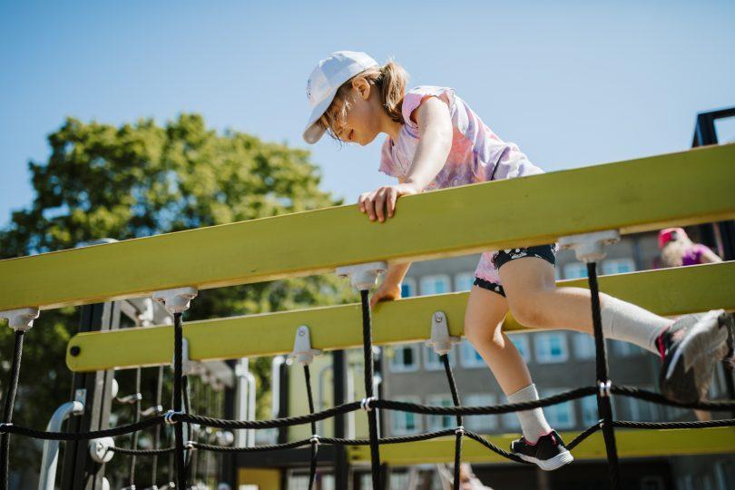 En flicka som klättrar i en klätterställning på en skolgård