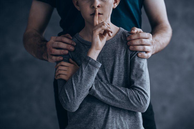 En pojke som har en tår på kinden och håller pekfingret framför munnen