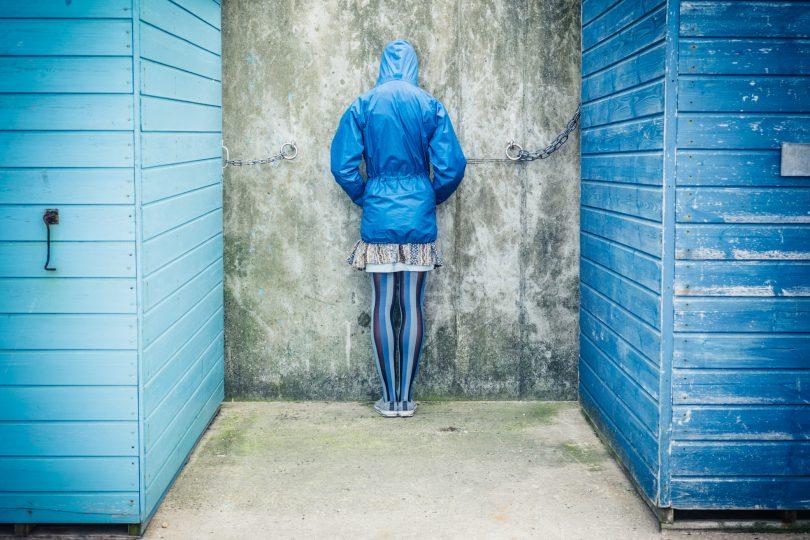 En person i blå rock som står med ansiktet mot väggen