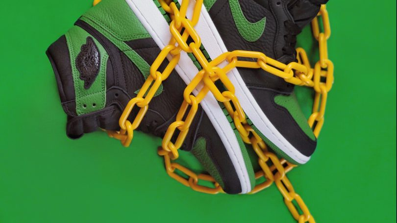Ett par gröna skor invirad i en gul kedja på ett grönt underlag