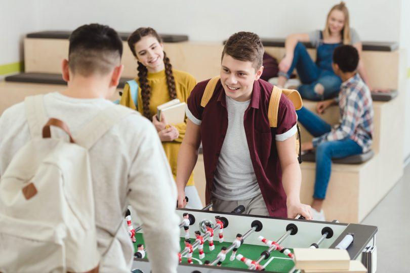 Två pojkar som spelar bordfotboll och en flicka tittar på