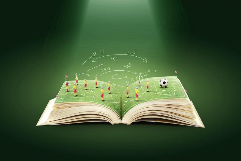 En öppnad bok med en fotbollsplan på mittuppslaget
