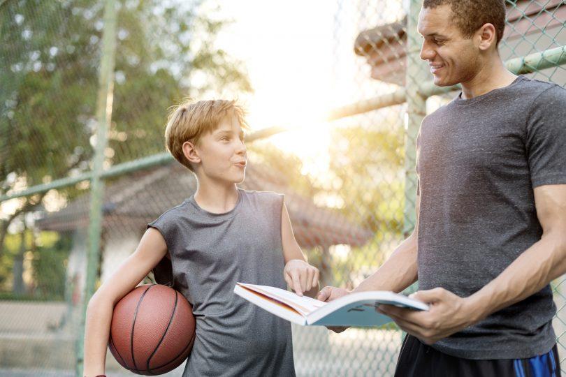 En ung pojke som står tillsammans med sin tränare och en basketboll under armen