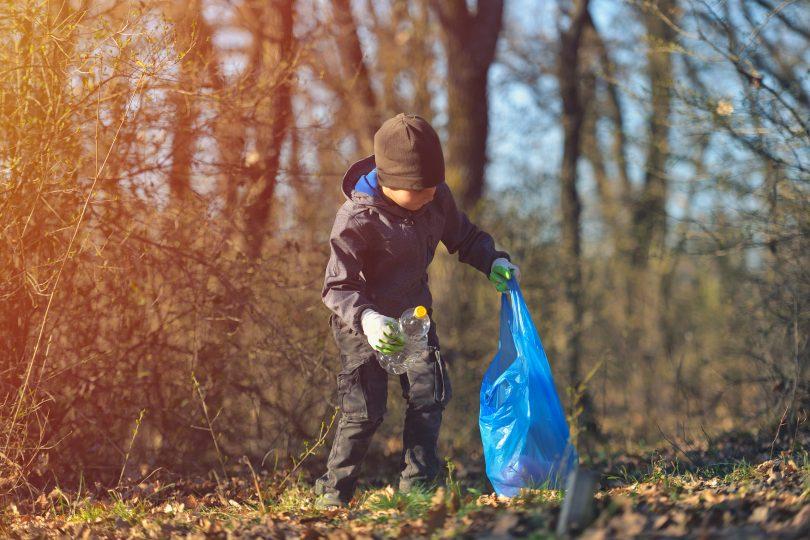 Barn som plockar skräp i naturen