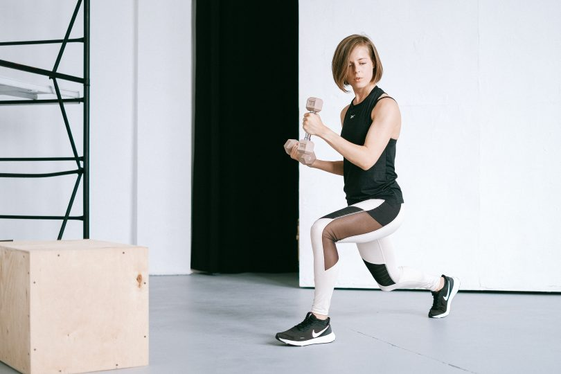 Kvinna som träna hemma med vikter