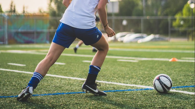 Kvinnlig fotbollsspelare som sparkar boll